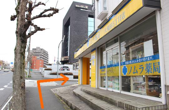 直進しますと黄色い看板のノムラ薬局さんがありますのでそこを右に曲がって直進して下さい。